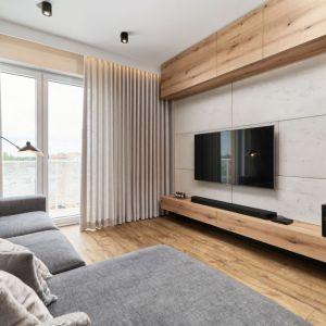 Ściana za telewizorem w salonie wykończona jest betonowymi płytami. Projekt: Monika Staniec. Fot. Wojciech Dziadosz