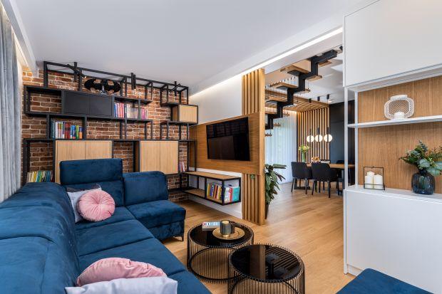 Dom o powierzchni 90 metrów kwadratowych został zaprojektowany dla czteroosobowej rodziny. Znajduje się w obrzeżach Krakowa w pięknej, zielonej okolicy. Wnętrze w stylu industrialnym doskonale łączy biel, czerń, kolor ciepłego dębu i nieco chł