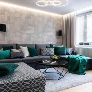 Główne miejsce w salonie zajmuje narożniki w szarym kolorze, który pięknie ożywiają dodatki w zielonym kolorze. Projekt: Dariusz Grabowski, Dagar Studio. Fot. Karolina Wargocka-Kusz
