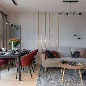 Szary salon ożywiają dodatki w bordowym kolorze. Projekt i zdjęcia: KODO Projekty i Realizacje Wnętrz