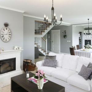 Ściany w jasnym, szarym kolorze w salonie w klasycznym stylu zestawiono z białą sofą. Projekt Beata Ignasiak. Fot. Bartosz Jarosz