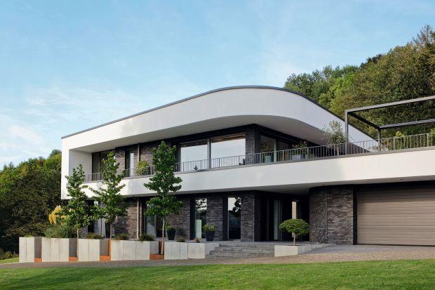Dom jednorodzinny powstał z zestawienia kontrastów między otwartymi i zamkniętymi przestrzeniami oraz strefami wypełnionymi światłem i ciemnymi, teksturowanymi materiałami. Wysoko izolowane cieplnie okna i drzwi przesuwne o dużej powierzchni oszk