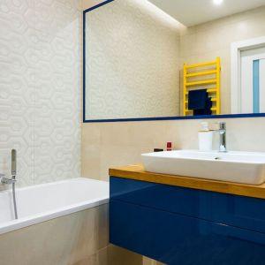 Kolorowa lakierowana szafka podumywalkowa  łazience z wanną. Projekt Krystyna Dziewanowska, Red Cube Design. Fot. Mateusz Torbus 7TH Idea.