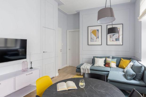 Nawet najmniejszy salon może być urządzony nietuzinkowo. By dodać mu charakteru, warto udekorować ściany, np. tę za kanapą, czy telewizorem.